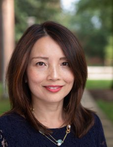 Charissa Cheah, an Asian American woman, smiles at the camera. She has shoulder length brown hair with light highlights. She has on a navy blue top and is wearing a necklace with a turquoise stone.