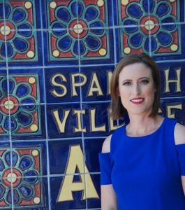 Erin Hogan is standing in front of street sign in Spain that consists of brightly colored ceramic tiles.